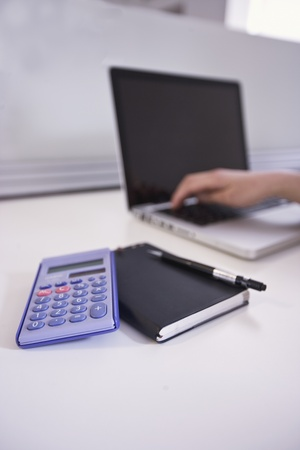 A notepad  calculator and laptop in an office Stock Photo - 12738435