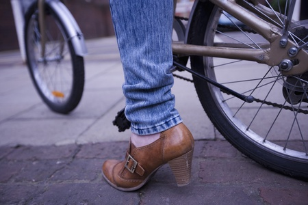 The bottom half of a bicycle and a ladies leg Stock Photo - 12738442