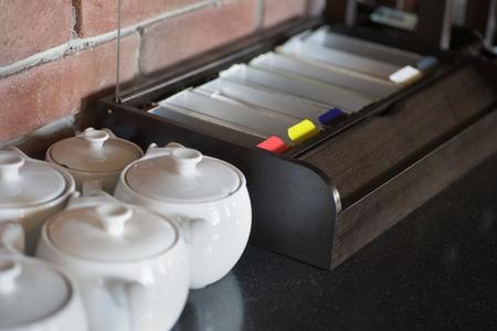 sachets: Little china teapots lined up next to tea sachets