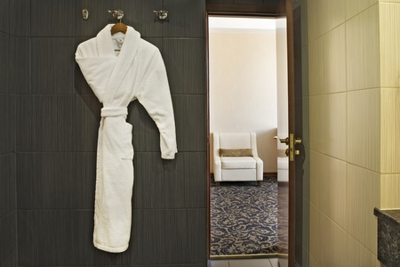 a white robe: Interior of a hotel room with a white dressing gown hanging up and the door open with a view through to the next room