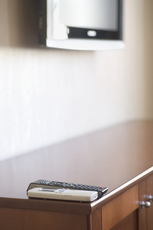 Two controls positioned on the corner of a cabinet with a television in the background Stock Photo - 12738463