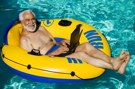 float tube: Senior Man on Float Tube Using Laptop LANG_EVOIMAGES