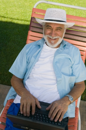 lawn chair: Senior Man in Lawn Chair Using Laptop LANG_EVOIMAGES