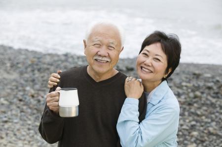 the ageing process: Senior couple at beach looking at camera