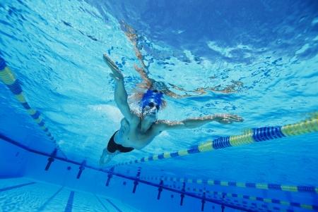 exerting: Man Swimming in Pool