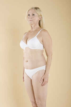 partially nude: Middle aged woman in white lingerie LANG_EVOIMAGES