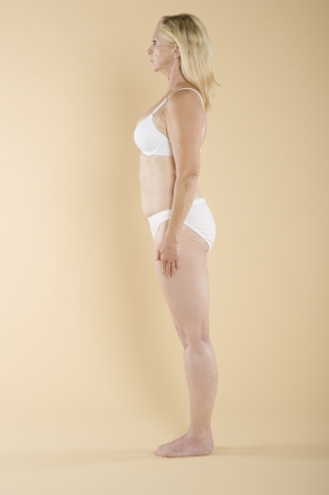 blonde underwear: Side view of a semi nude woman in white lingerie
