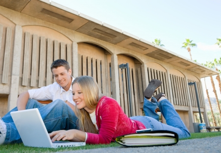 high school series: Two students using laptop outdoors LANG_EVOIMAGES