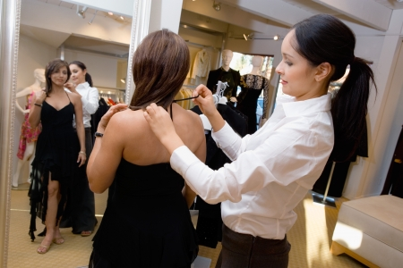 evening wear: Saleswoman assisting customer with dress side view