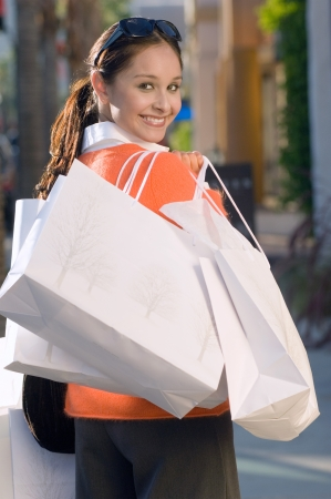 retail therapy: Woman holding shopping bags portrait LANG_EVOIMAGES