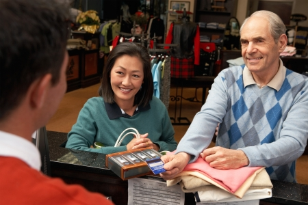 service card: Couple Paying for golf apparel in golf store by credit card at checkout counter