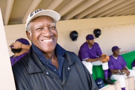 baseball dugout: Entrenador de b�isbol en piragua sonriendo (vertical)