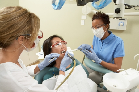 Two dentists examining female patient in surgery Stock Photo