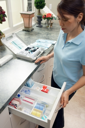 Dental hygienist opening supply drawer in clinic
