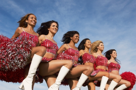 adult cheerleader: Cheerleaders in a row kicking legs LANG_EVOIMAGES