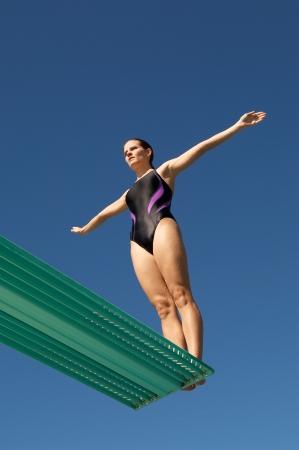 Femme sur le point de plonger vers l'arrière d'un plongeoir