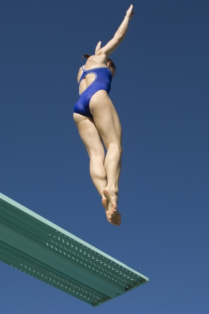sky diving: Female swimmer jumping on diving boards