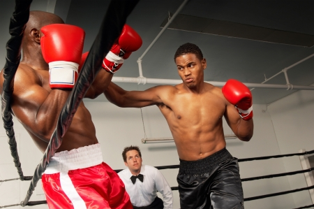 two people with others: Boxers fighting in ring with referee watching LANG_EVOIMAGES