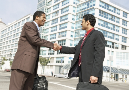 racially diverse: Businessmen Shaking Hands LANG_EVOIMAGES