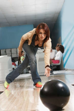 bowling alley: Young woman releasing bowling ball portrait
