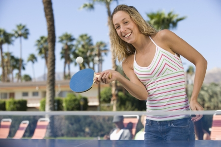 whites: Young woman playing table tennis portrait