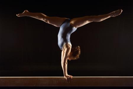 gimnasia: Gimnasta (13-15) haciendo parada de manos dividida en equilibrio vista lateral del haz