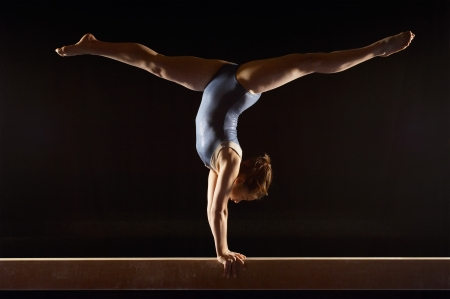Gymnast (13-15) doing split handstand on balance beam side view