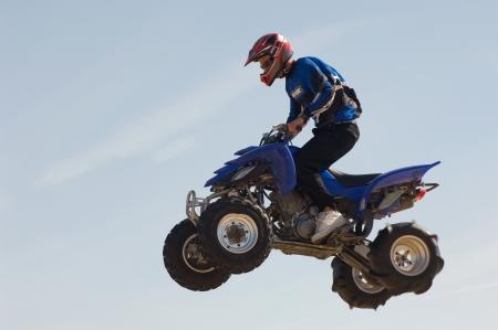 midair: Man riding quad bike in mid-air against blue sky close up