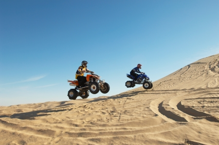 Men doing wheelies on quad bikes in desert Stock Photo - 18884322