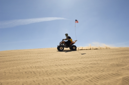 20 to 25 year olds: Young Man Riding ATV Over Sand Dune