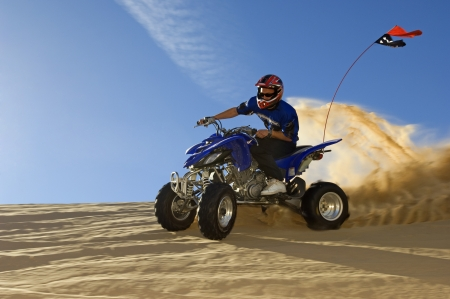 manoeuvre: Young Man Riding ATV Over Sand Dune