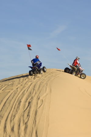 20 to 25 year olds: Young Men Riding ATVs Over Sand Dunes