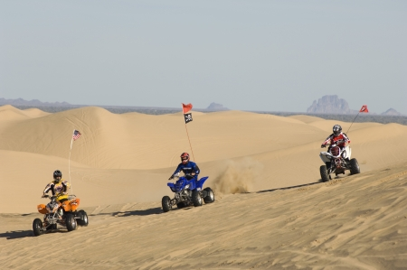 20 to 25 year olds: Three Young Men Riding ATVs on Dunes