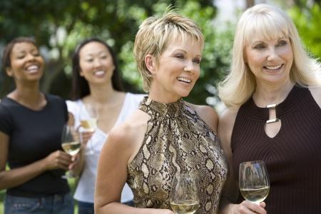 屋外ワインを飲む女性の友人 写真素材