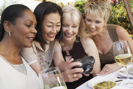 garden party: Four elegant women at garden party looking at photos on digital camera