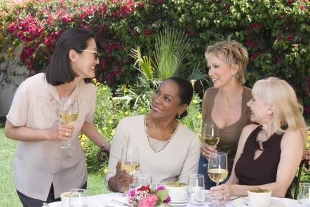 屋外のテーブルでワインを飲む女性の友人 写真素材