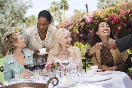 屋外のテーブルで飲む女友達 写真素材