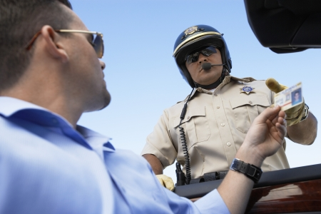 fortysomething: Man Handing a Police Officer her License LANG_EVOIMAGES