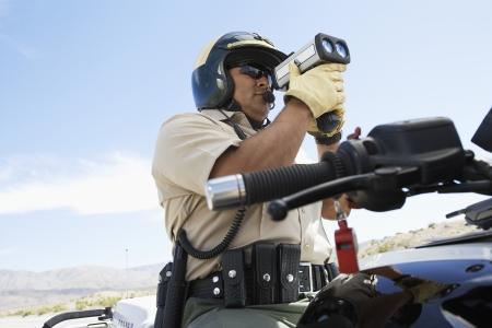 radar gun: Oficial de Polic�a Holding Gun Radar LANG_EVOIMAGES