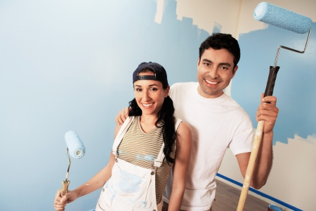 home improvement: Couple with paint rollers portrait