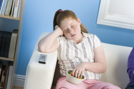 childhood obesity: Overweight girl sleeping on sofa