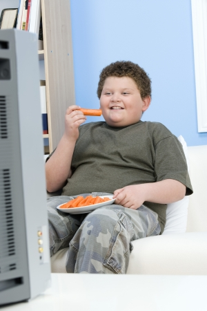 childhood obesity: Overweight boy watching television, eating healthily LANG_EVOIMAGES