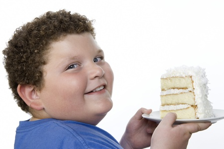 preteen boy: Overweight  boy holding plate with big piece of cake. LANG_EVOIMAGES
