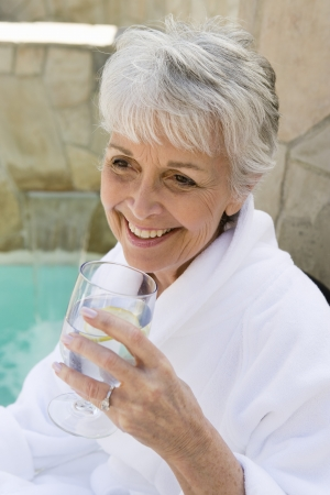the ageing process: Senior woman drinking outdoors