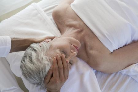 the ageing process: Senior woman having head massage