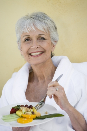 healthily: Portrait of senior woman eating healthily LANG_EVOIMAGES