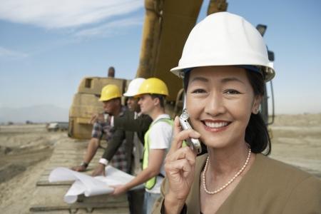 relaciones laborales: Agrimensor utilizando teléfono celular en el sitio de construcción