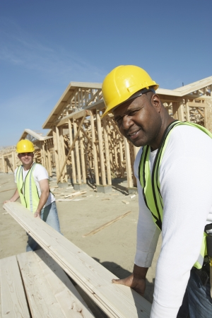 Construction Workers Stacking Timber Stock Photo - 18884272