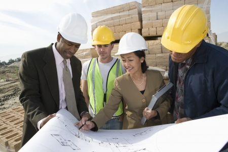 site preparation: Two architects and two construction workers standing on construction site holding blueprints
