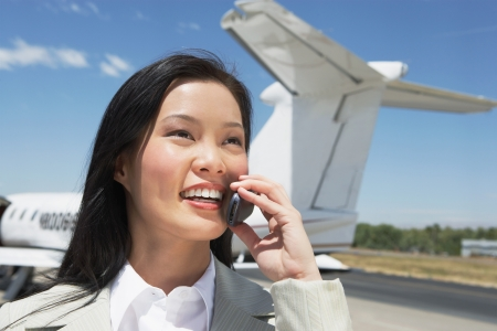 Smiling Businesswoman standing outside Airplane talking on mobile Stock Photo - 18884263